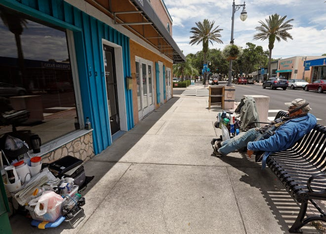 Homelessness is no longer just a Daytona Beach problem. City officials in New Smyrna Beach have been debating what they should do to help the homeless as well as residents who say they've had problems with homeless people coming onto their property and stealing from them. Pictured is a man relaxing on a bench along Canal Street on Thursday.