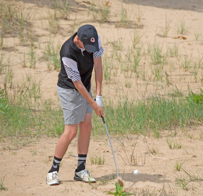 Quincy's Brandt Neely, shown here blasting out of the bunker, paced the Quincy effort with an 8th place finish