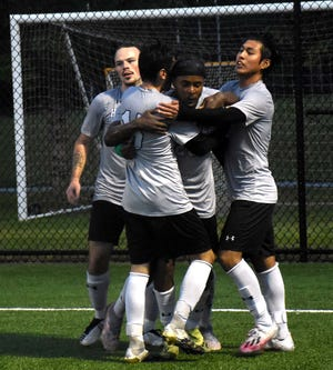 Generals Justin Greiner, Max LaRose and Christ Valle (from left) swarm Herkimer College teammate Alex Charles after Charles scored the first goal against Monroe College during the second half of Wednesday's NJCAA Division III men's soccer quarterfinal match.