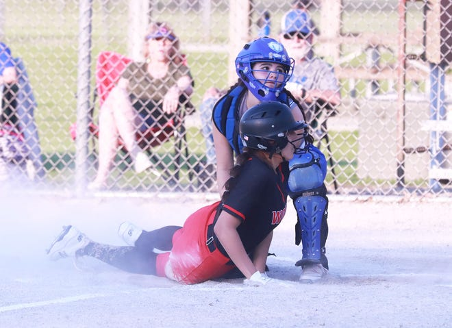 Danville's Gracie Walker and Winfield-Mt. Union's Melina Oepping look to the umpire for the call at home plate in the Wolves' 12-0, three-inning win over the Bears at Winfield Wednesday evening.