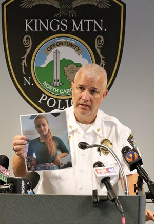 """Kings Mountain Police Assistant Chief Chris Moore holds a photo of missing teen, Amelia """"Amy"""" Upton during a press conference held at the Kings Mountain Police Department Thursday afternoon, June 3, 2021. Upton was found safe Thursday evening."""