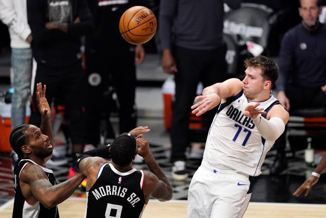 Dallas Mavericks guard Luka Doncic, right, passes the ball over Los Angeles Clippers forward Kawhi Leonard, left, and forward Marcus Morris Sr. during the second half in Game 5 of an NBA basketball first-round playoff series Wednesday in Los Angeles. The Mavs return to Dallas for Game 6 on Friday night.