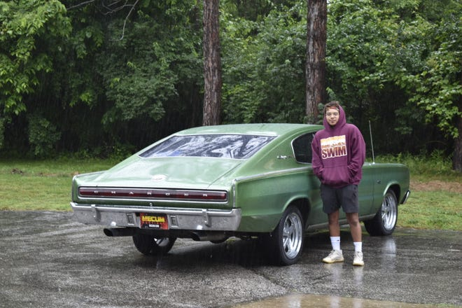 Luis Brown stands beside his 1966 Dodge Charger this week during a steady downpour.