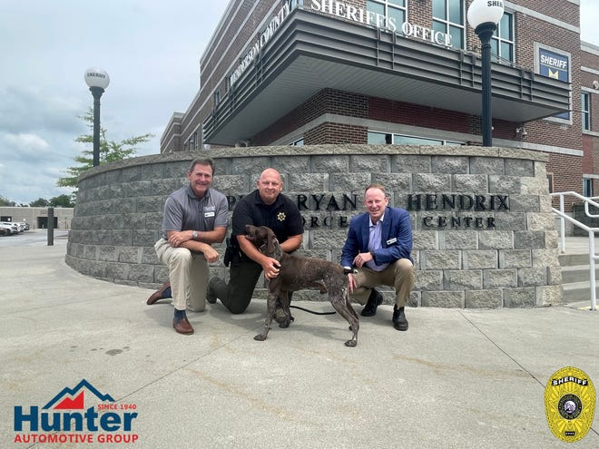 K-9 Officer Kevin Holden (center) poses for a photo with the Hunter, a donation from the owners of Hunter Automotive, Randy Hunter (left) and Tom Hunter (right).
