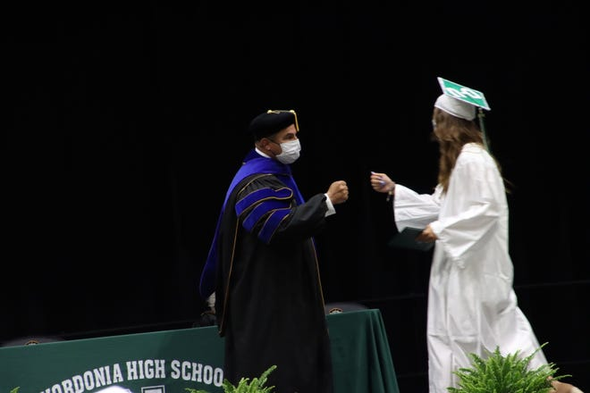 Dr. Joe Clark gets ready to give a fistbump to one graduating senior during the commencement ceremonies May 25.