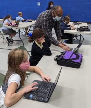 Kent State University Technology Director for RCET's and AT&T classrooms, Thomas McNeal assists fifth graders Daphne Mann and Lucy Anderson with programming their Edison robots.