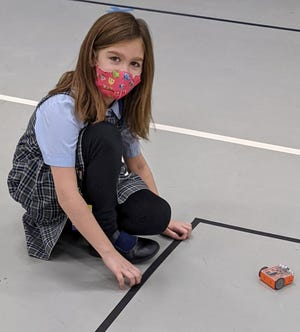 St. Joseph Parish School student Maggie Ruegg experiments with the different functions of the Edison robot that she previously coded.