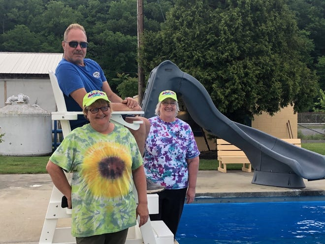 Parks and Recreation commissioner Ron Metcalf sits atop the new lifeguard chair, while Save the Keyser Pool Committee members Missy Cummings and Lynn Robinson keep their feet on the ground. In the background is the new water slide which will make it's debut when the John R. Shelton Swimming Pool opens Saturday.