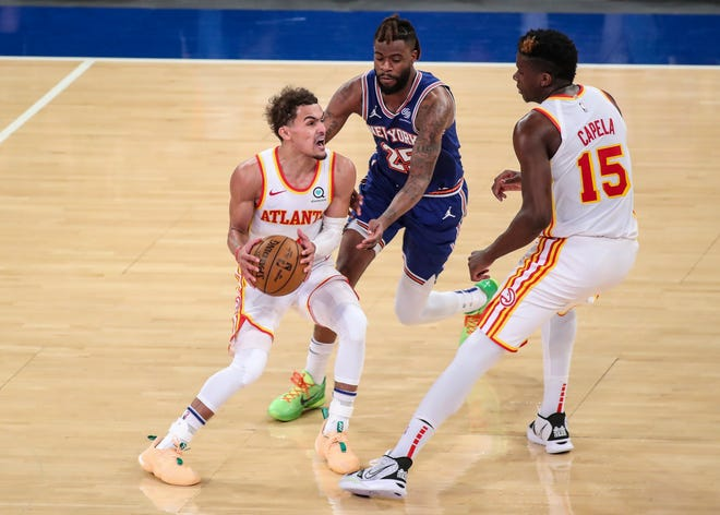 Atlanta Hawks guard and former OU star Trae Young, left, looks to drive past New York Knicks forward Reggie Bullock (25) during Wednesday night's Game 5 of an NBA playoff series.