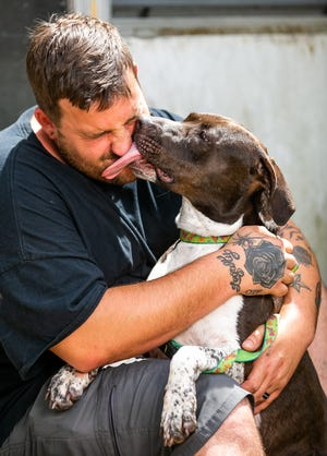 """Warren Robbins gets a kiss from 6-year-old Aquarius on Thursday at their home in Summerfield. """"We went to adopt a cat and came home with a dog."""" Robbins said with a laugh. """"I'm really a big dog person. We have a 2-year-old and baby on the way. She was the only dog not freaking out. We took her out to the playpen and there was no looking back."""""""