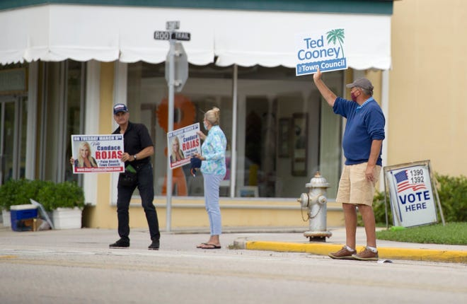 Supporters of Town Council candidates Ted Cooney and Candace Rojas campaign near St. Edwards Parish Hall during the town's general election March 9.