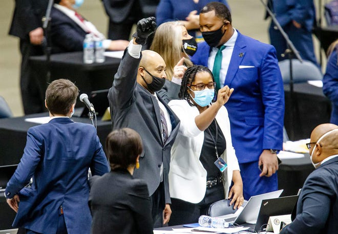 Rep. Justin Slaughter, D-Chicago, holds up his fist while wearing a black glove after the criminal justice reform bill passes the Illinois House during the lame-duck session of the Illinois House of Representatives in January at the Bank of Springfield Center.