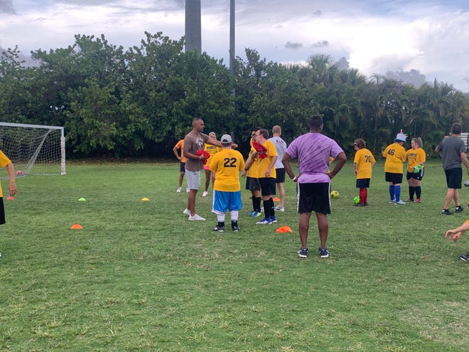 Special Olympics Palm Beach County Strikers coach Daniel Mueller, left, goes over a drill with his players during a practice Wednesday, June 2, 2021.