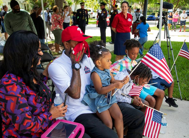 Marine Lance Cpl. Jason Chong  wipes his eyes Thursday while sitting with his family at a ceremony where he received a mortgage-free home in Lake Worth Beach.