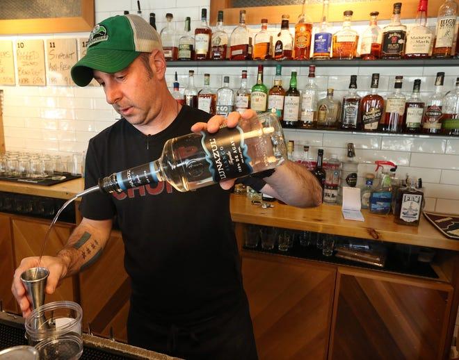 Vito Lantz, beverage director at Chomp Kitchen & Drinks in Providence, prepares to-go drinks.