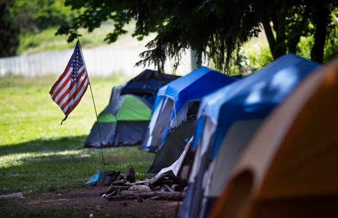 """The U.S. flag flies near an encampment of tents in Skinner Park over Memorial Day weekend. The city of Eugene is seeking feedback on proposed """"Safe Sleep Sites"""" where people experiencing homelessness can legally camp or park their cars."""