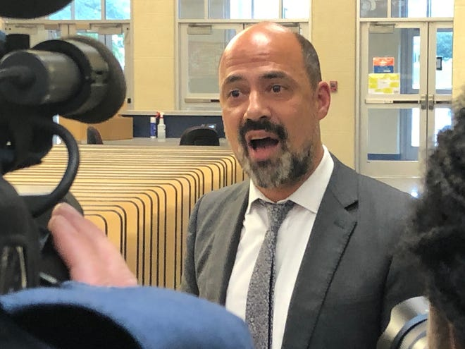 Attorney Peter Pattakos talks with the media while the Canton City Board of Education meets in executive session regarding the McKinley High football team.
