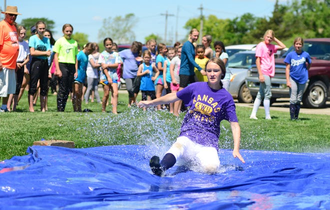 Brooke Banninger, 13, member of the Bolts softball team slides feet first onto the wet tarp during the fun and fundamental summer softball camp at the Bill Burke Sports Complex on Thursday.