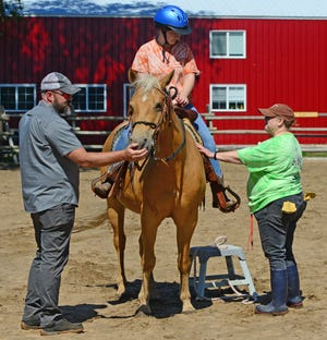 Brett Graves pets the nose of his Palomino horse named Leggs as junior volunteer Courtney McCullough, of Salina, gets instructions from adult volunteer Joyce McNeal, of Salina, before riding around the arena at the Shiloh Ranch Ministries located ten miles north of Solomon.