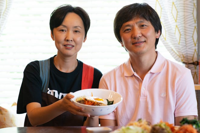 Sunyoung Cheong, a University of Kansas professor, and husband Sangyoub Park, a Washburn University professor, hold up a bowl of freshly prepared bibimbap Thursday at their home in Topeka.