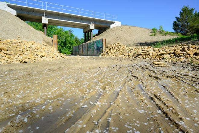 Muddy ruts from bike traffic fill with water Thursday morning at this portion of the Landon Trail by Kansas Ave. and S.W. 33rd St. where a BNSF railroad bridge was built and pavement torn up.
