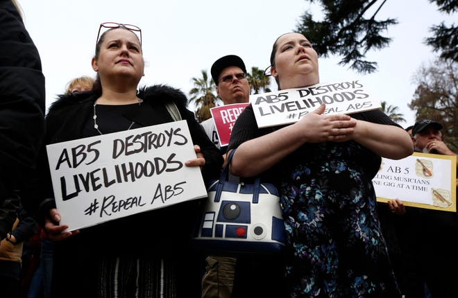 Independent contractors Jennifer Young, left and Erika Osburn, right, joined others at a rally in support of a measure to repeal a California law that makes it harder for companies to label workers as independent contractors, in Sacramento, Calif., in 2020.