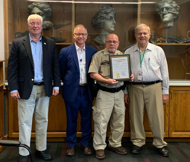 Tuscarawas County Commissioners Al Landis (left), Chris Abbuhl and Kerry Metzger gathered to honor Terry Warner on his retirement.