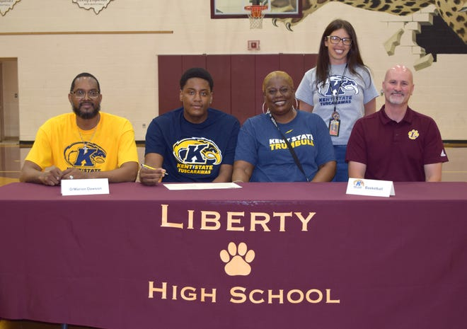 Signing a letter of intent is O'Marion Dawson(second from left) sitting between Levon Lamb, Youngstown Liberty Head Basketball Coach, Dawson's mother Toya and Liberty Athletic Director Eric Buckingham. In the back row is Terri Long, Academic Coach at Youngstown Liberty.