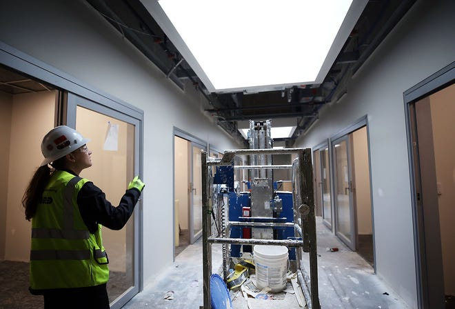 Colleen Cross, a project engineer with Corna Kokosing Construction Co., shows what will become the district offices in Grandview Heights Schools' new building that eventually will house students in grades 4-8.
