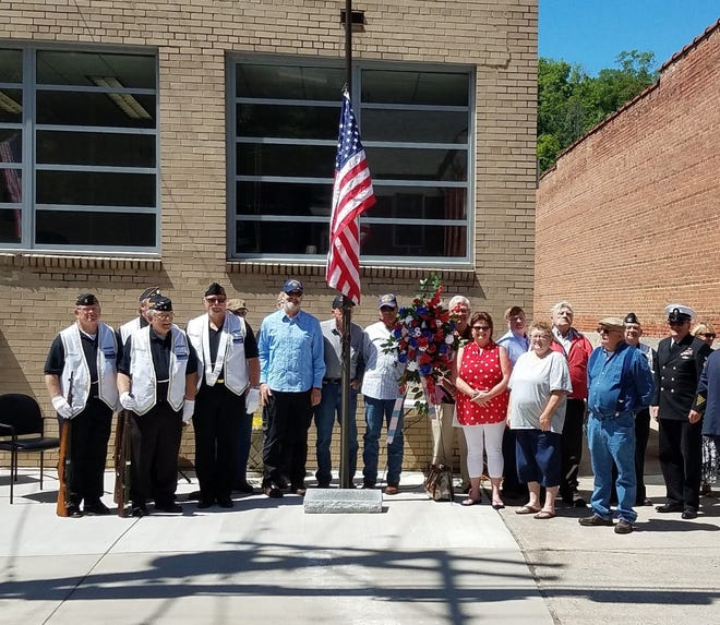 The North Carolina Submarine Veterans (NCSubVets) and a delegation of Madison County veterans pose for a photo with the wreath and flagpole honoring Jack Wallin during Marshall Town Board's Memorial Day celebration of the former mayor.