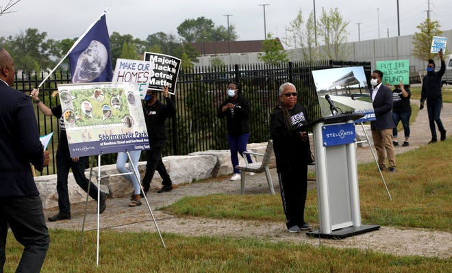 Stephanie Broddie, a school teacher at Southeastern High School stops talking as concerned citizens and residents of Beniteau Street march and chan passing by her during the Stellantis press conference and ground breaking at the corner of Kercheval and Beniteau in Detroit for the $1 million green initiative and education pavilion at Stormwater Park on Thursday, June 3, 2021.