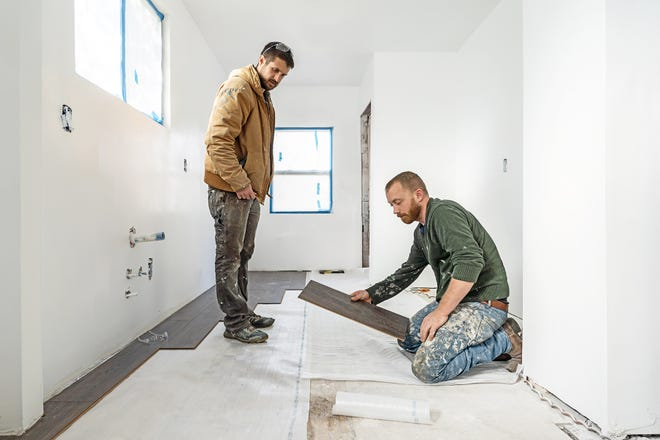 """Keith Bynum and Evan Thomas laying flooring in a scene from HGTV's """"Bargain Block."""""""