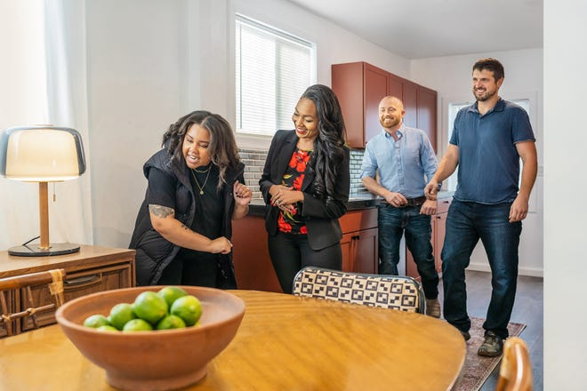 """Shea Hicks-Whitfield, Keith Bynum and Evan Thomas show a new homeowner her renovated dining room on  HGTV's """"Bargain Block."""""""