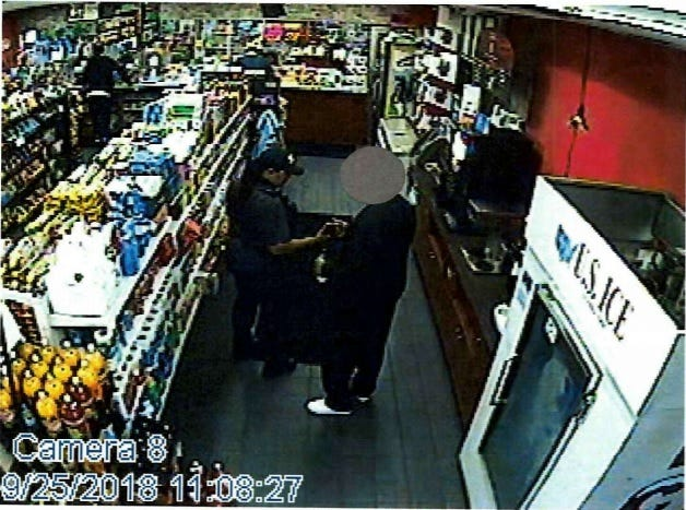 The FBI says this 2018 gas station video shows a Highland Park police officer accepting $300 from an undercover informant for allegedly setting up a drug deal.