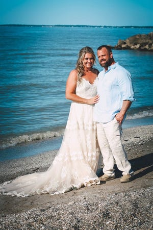 """When storms threatened to ruin Holly (Weber) Baynes' dream of a perfect destination wedding in Port Clinton, she turned to """"The Talk of Port Clinton (Original)"""" Facebook page for advice. Holly was overwhelmed by the community response which helped make her wedding better than she hoped. Here, Holly and her new husband, Greg Bayne, pose on the beach that was underwater just two days before."""