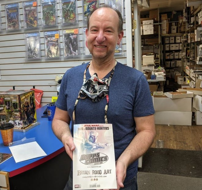 """Chris Rupp of Rupp's Comics holds his store's exclusive variant cover to the new Boba Fett book """"War of the Bounty Hunters."""""""