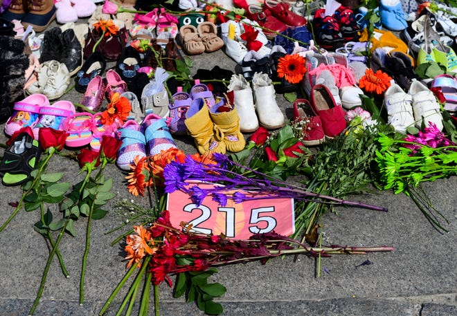 Flowers, children's shoes and other items rest at a memorial in Ottawa in recognition of the discovery of children's remains.