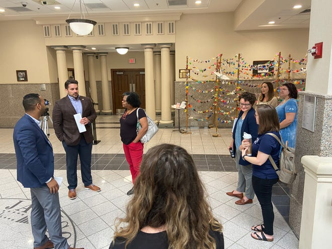 Jackson Mayor Scott Conger and United Way of West Tennessee Director Matthew Marshall (far left) speak with others involved with the Cities for Financial Empowerment program before an announcement about the plan's blueprint unveiling on Wednesday at City Hall.
