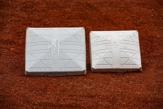 Bases sit side by side for size comparison in the dirt before a recent game at Louisville Slugger Field in Louisville, Ky. In an attempt to reduce player collisions and injuries, the size of the first, second and third bases in Triple-A was increased from 15 to 18 square inches.