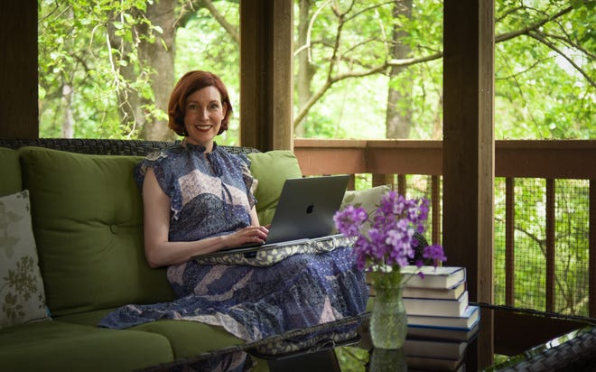 """Writer Darcy Woods pictured Wednesday, June 2, 2021, in her """"summer writing room"""" on the back deck of her home in Williamston."""