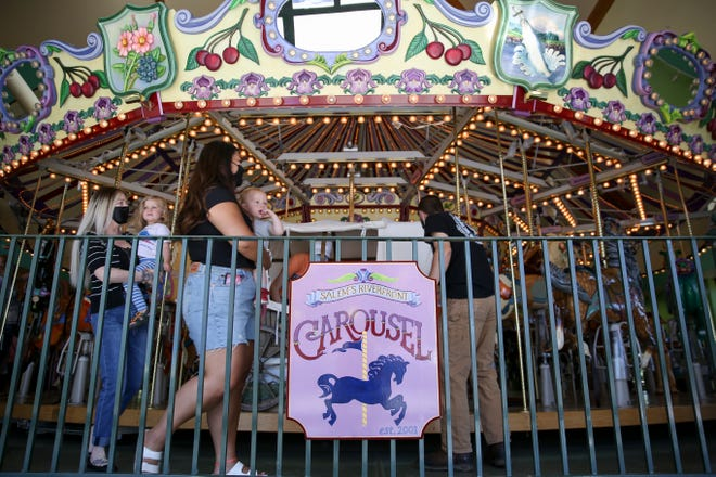 Families visit the Salem Riverfront Carousel on Thursday. The carousel is set to celebrate its 20th birthday on Saturday.