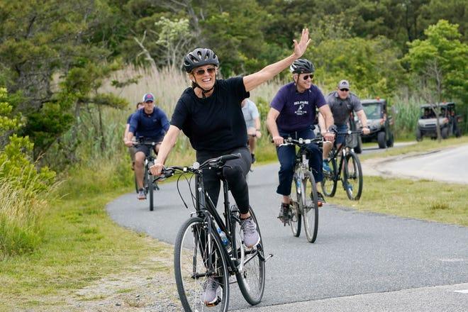 First lady Jill Biden waves as she rides her bike with President Joe Biden near Rehoboth Beach, Del., Thursday, June 3, 2021. The Bidens are spending a few days in Rehoboth Beach to celebrate first lady Jill Biden's 70th birthday.