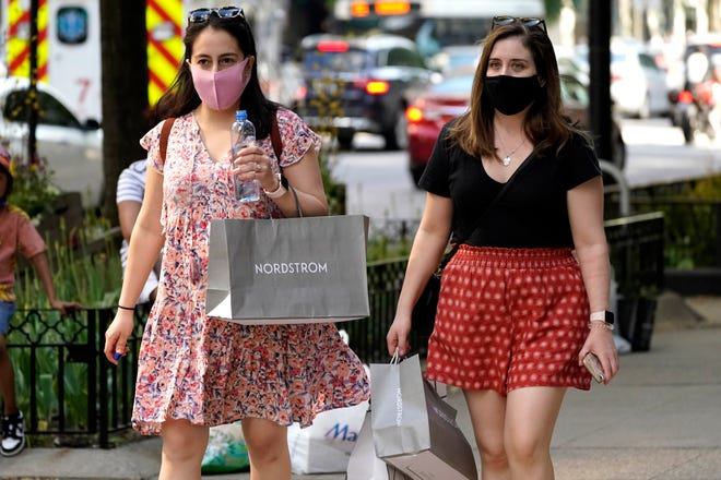 Shoppers carry their bags as they walk along a shopping district on Michigan Avenue in downtown Chicago on May 22, 2021.