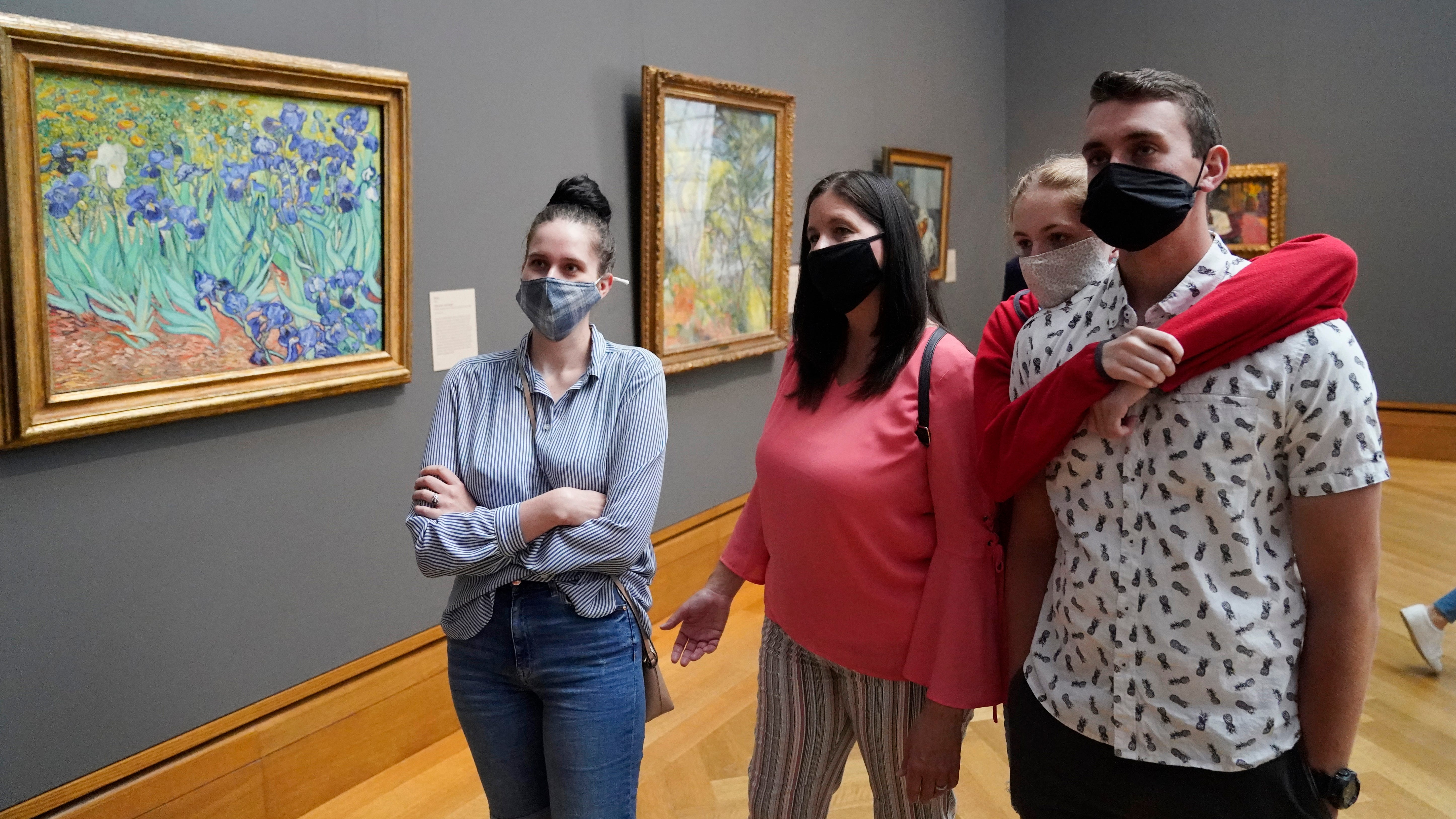Visitors wear masks as they view art, including Vincent van Gogh's