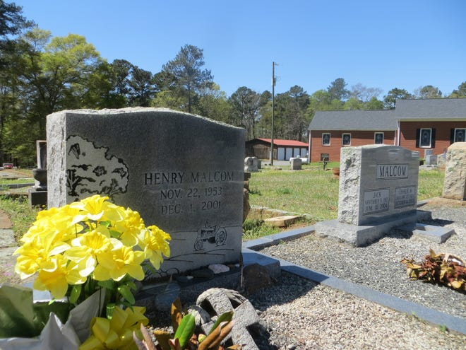 The grave of Henry Malcom in the Greene County community of Greshamville, next to his parents who died about two years after his unsolved slaying.