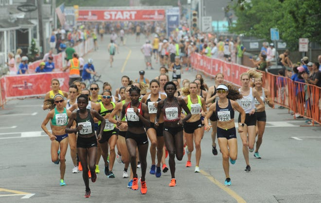 The elite women runners take off for the start of the Falmouth Road Race in August 2019.