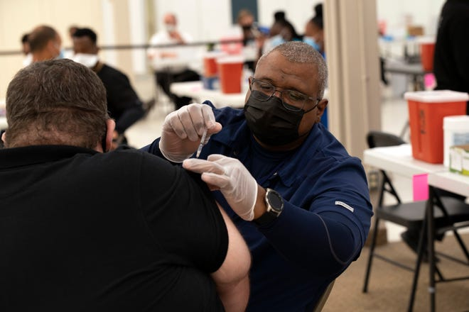 A resident receives a COVID-19 vaccine earlier this year at the Lake Square Mall in Leesburg. [Cindy Peterson/Correspondent]
