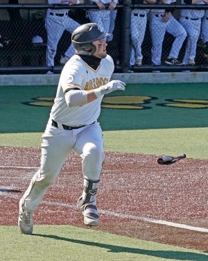 Adrian College's Gunner Rainey watches the ball as he hits a home run during a game in the 2021 season.