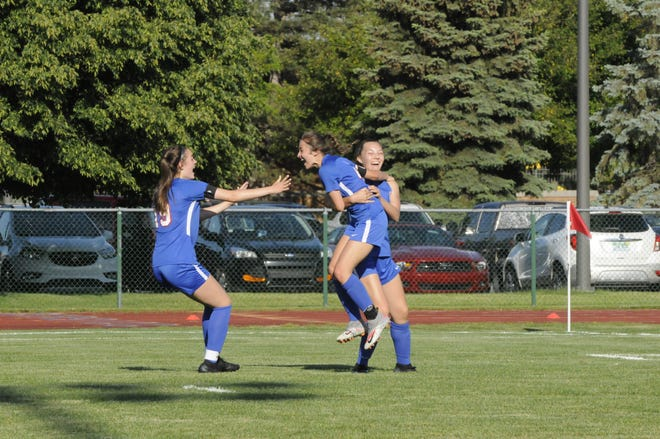 Lenawee Christian's Janae Good (middle), Kylie Summer (right) and Olivia Durbin (left) celebrate a goal during Thursday's Division 4 district championship against Manchester.