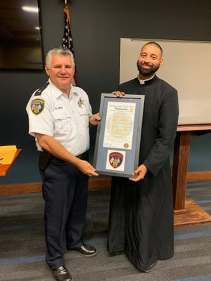 Sheriff Bobby Webre presents the Honorary Sheriff certificate to Father Josh Johnson of Holy Rosary Catholic Church.